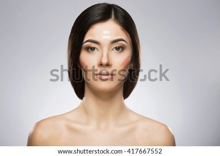 Girl with professional contour and highlight makeup. Contouring face make-up applying sample. Hair at the back. Beauty portrait, head and shoulders, full face. Indoor, studio - stock photo