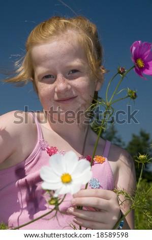 Girl with red hair is plucking flowers in the garden