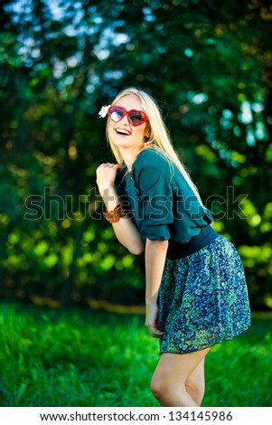 girl with red heart glasses posing outdoor - stock photo