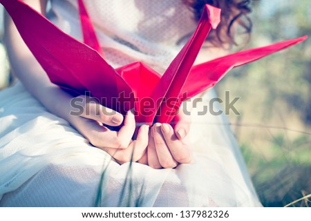 Girl with red origami crane - stock photo
