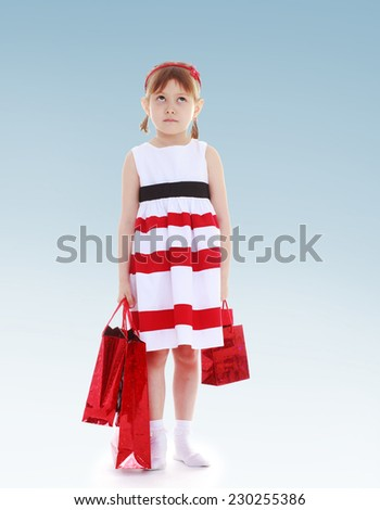 Girl with red packets for shopping in the hands of.charming little girl - stock photo