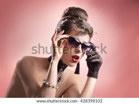 Girl with retro - hairstyle, sunglasses, gloves, very similar to the famous actress - stock photo
