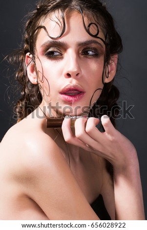 girl with saliva dripping from wet, open mouth on bottle in hand. Fashionable woman with evening makeup and stylish, long, brunette hair on grey background. Anticipation. Beauty salon