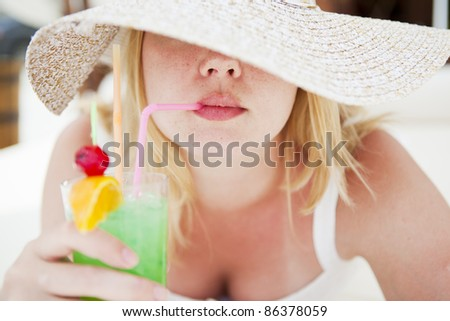 Girl with sexy lips drinking a cocktail, hat turned a blind eye - stock photo