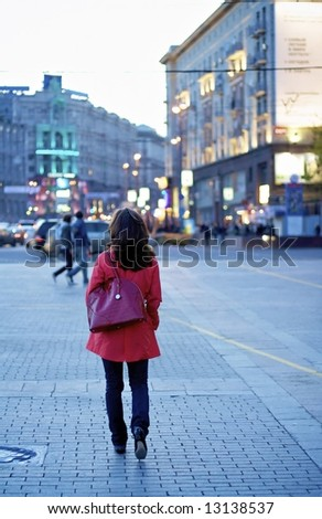 Girl with shopping bag in downtown in the evening - stock photo