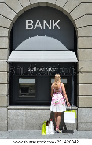 Girl with shopping bags at ATM - stock photo