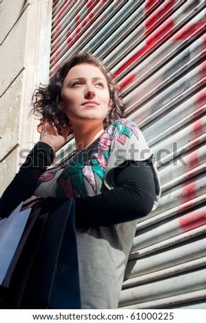 Girl with shopping bags at graffiti wall - stock photo