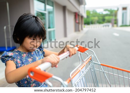 Girl with shopping cart. - stock photo