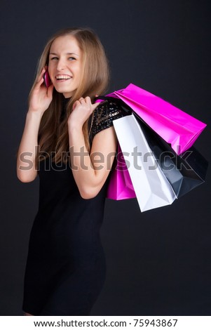 Girl with shopping on the phone and smiling - stock photo