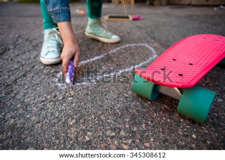Girl with skateboard drawing on asphalt with street chalk - stock photo