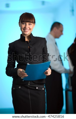 Girl with smile and with blue folder and men - stock photo