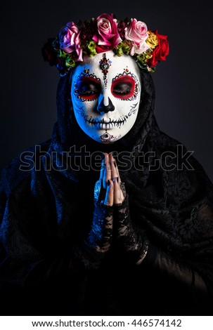 Girl with sugar skull make up with flowers at black background