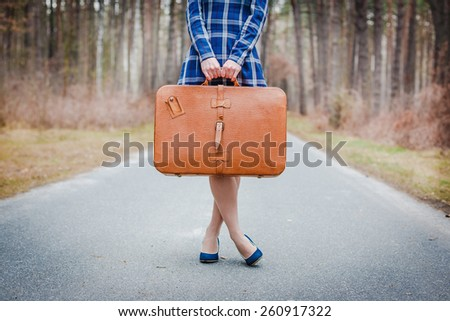 girl with suitcase on the road - stock photo