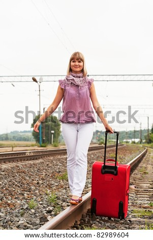 girl with suitcase walking along rail - stock photo