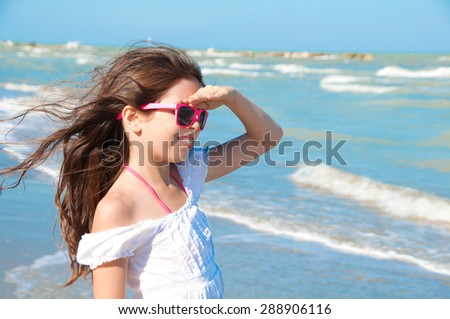 Girl with sun glasses looking on the sea - stock photo