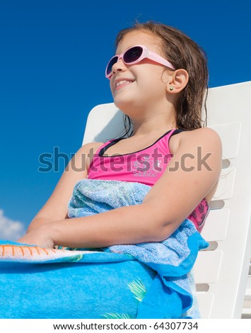 Girl with sunglasses relaxing in a deck chair - stock photo