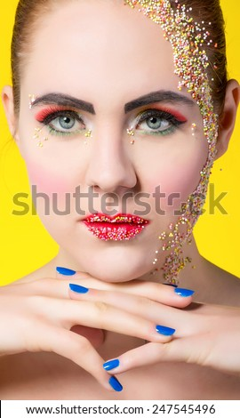 Girl with sweets in colorful makeup - stock photo
