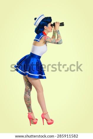 girl with tatoos dressed sailors looking through binoculars, retro style - stock photo