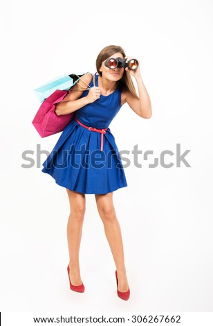 Girl with the shopping bags looking through the binoculars