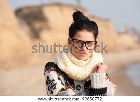 Girl with thick-rimmed glasses standing on seaside