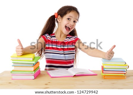 Girl with thumbs up sign sitting on the table with stack of books, isolated on white - stock photo