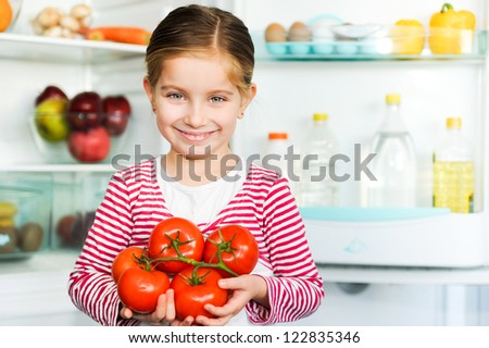 girl with tomatos on background refrigerator