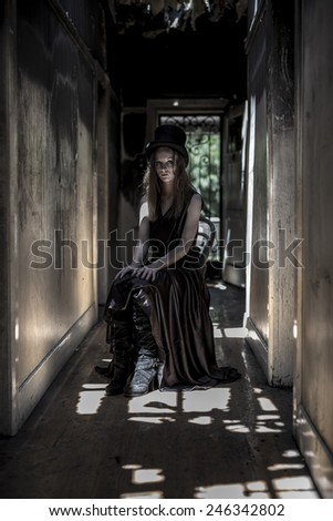 Girl with top hat in ruined hallway.