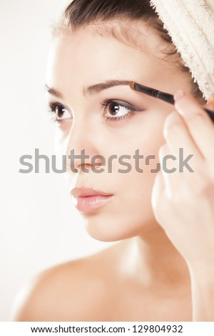 girl with towel on head draws her eyebrows with a Eye brow brush
