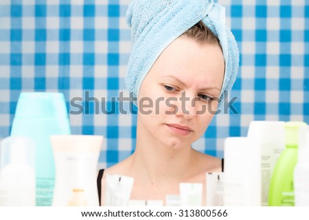 Girl with towel on her head is looking at cosmetic products in bathroom. Skincare and beauty concept. Frontal portrait - stock photo