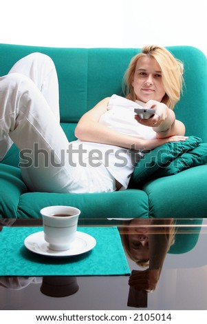 Girl with TV remote (focus on remote) looking at camera - stock photo