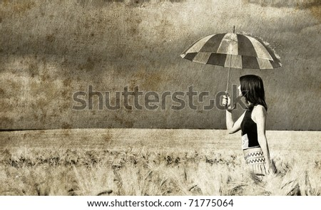 Girl with umbrella at field. Photo in old retro style.