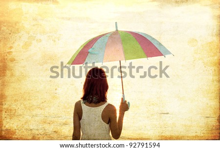 Girl with umbrella at sea coast. Photo in old image style. - stock photo