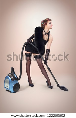 Girl with vacuum cleaner posing for camera