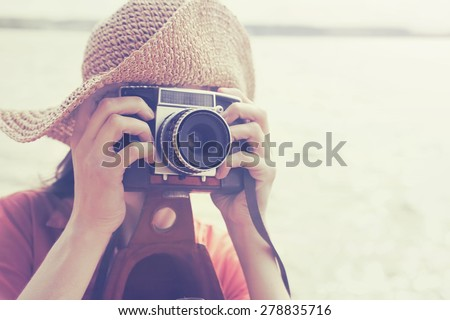 girl with vintage camera taking photo, filtered, copy space - stock photo