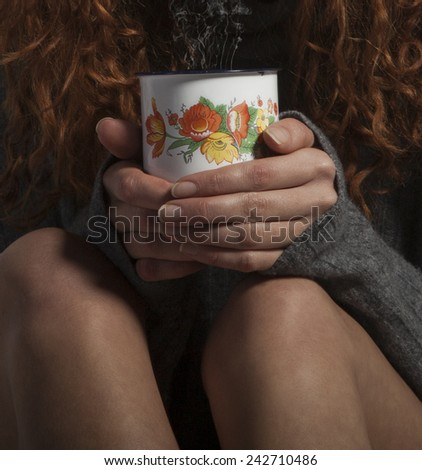 Girl with warm sweater holding cup of coffee, hot chocolate or tea. - stock photo