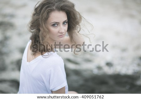 Girl with wavy hair on the beach with black sand in a light white top and denim varieties