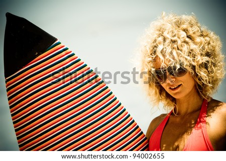 girl with white hair posing with surf on the shore of the island of Mauritius - stock photo