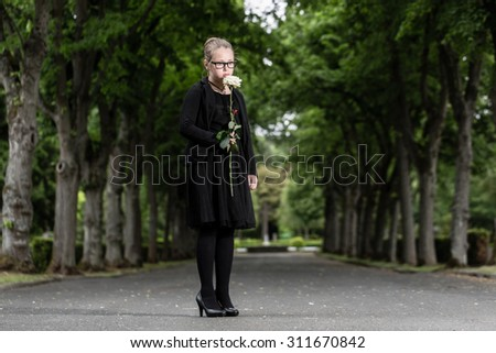 girl with white rose mourning deceased on graveyard being an orphan now - stock photo