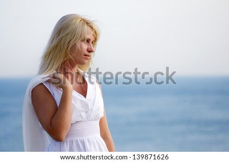 Girl with white scarf standing and looking into the distance at sea