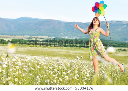 girl with windmill walking by the daisy field