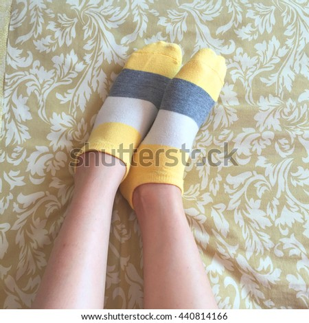 Girl with yellow striped socks, sleeping in bed great for any use. - stock photo