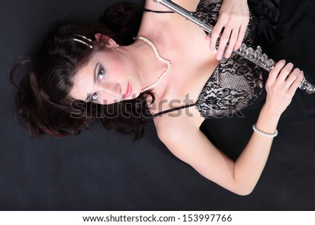 girl woman plays the flute on a black background - stock photo