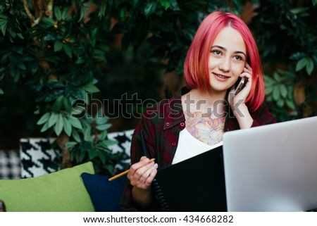 girl working in a cafe using a laptop computer and a notebook and talking on the phone