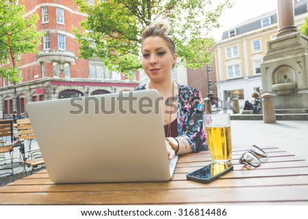 Girl working on her computer outdoor. She is writing on the keyboard while sitting at open air. There are a beer, a smart phone and a pair of glasses on the table. - stock photo