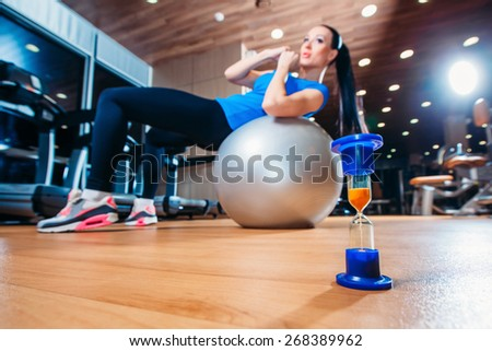 girl working out at the gym with a ball,  in the foreground of an hourglass , time concept to practice - stock photo