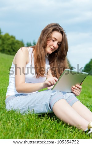 Girl working with tablet sitting in park on gras.
