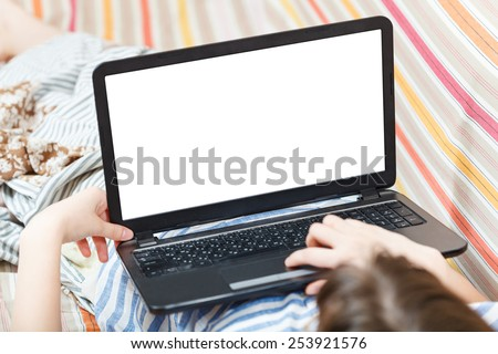 girl works on laptop with cut out screen in living room - stock photo