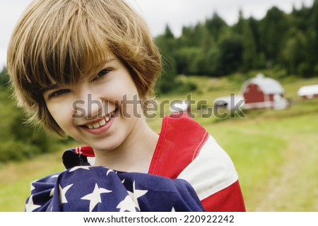 Girl wrapped in American flag on farm - stock photo