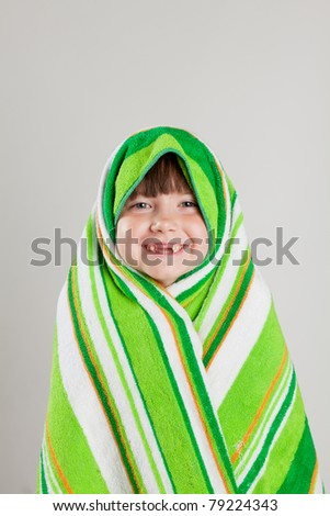 Girl wrapped in towel, smiling with baby teeth dropped out - stock photo