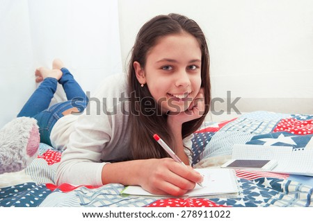 Girl writes a note lying on the bed - stock photo